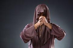 Il monaco nel concetto religioso su fondo grigio Fotografia Stock