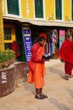 Il monaco nepalese che sta al tempio di Boudhanath per riceve la donazione immagine stock