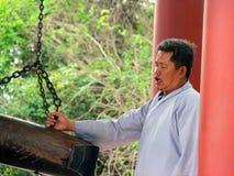 Il monaco suona la campana immagine stock