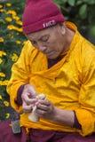 Il monaco tibetano ha scolpito la figura del tsampa della farina di orzo della divinità per cerimonia religiosa buddista in Himal Fotografie Stock