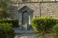 Il monumento è una fonte di acqua, scolpita dal basalto, in un parco vicino ad una parete di pietra situata intorno al monastero  fotografia stock libera da diritti