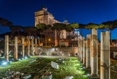 Il monumento di Vittorio Emanuele II alla notte, come veduta dalla basilica Ulpia rovina, a Roma, l'Italia Fotografie Stock Libere da Diritti