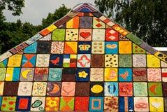 Il mosaico ha coperto di tegoli il tetto con le maschere colorate Fotografia Stock