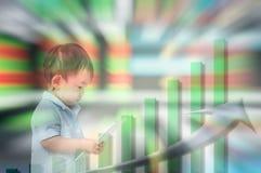Il mosso dell'inizio asiatico del bambino da imparare circa investe con la compressa in sua mano sul fondo di riserva vago del bo fotografie stock