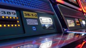 Il moto della donna inserisce i soldi sullo slot machine dentro il casinò stock footage