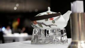 Il moto di tè caldo su moto della sfuocatura e della tavola della gente gode del pasto stock footage