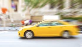 Il moto ha offuscato il taxi giallo su una via della città Fotografia Stock