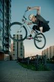 Il motociclista che salta tramite la rete fissa Fotografia Stock