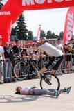 Il motociclista di prova resta nell'equilibrio sopra la donna Fotografia Stock Libera da Diritti