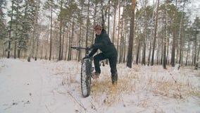 Il motociclista estremo professionale dello sportivo sta una bici grassa in all'aperto Il ciclista si adagia nella passeggiata de stock footage