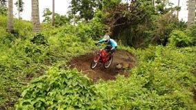 Il motociclista fa concorrenza durante in discesa ed evento della concorrenza di ostacolo video d archivio