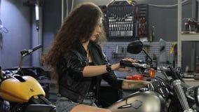 Il motociclista femminile mostra il suo pollice su sul motociclo video d archivio