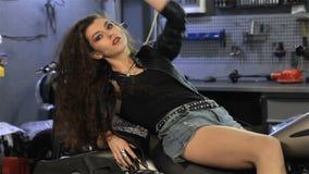 Il motociclista femminile si trova indietro sul sedile del motociclo video d archivio