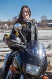 Il motociclista grazioso caucasico della ragazza che esamina la macchina fotografica, si siede sulla motocicletta, tenentesi per  fotografie stock