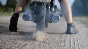Il motociclista guida via su un motociclo lungo una strada sabbiosa video d archivio