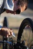 Il motociclista lubrifica la catena della bicicletta Fotografia Stock