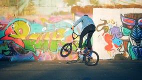 Il motociclista maschio salta fa le acrobazie, saltanti, movimento lento