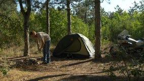 Il motociclista raccoglie la legna da ardere per un falò in foresta vicino al campo della tenda stock footage