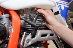 Il motociclista sostituisce, controlli che candela d'accensione dentro un motociclo immagini stock libere da diritti