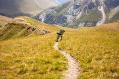 Il motociclista spinge la sua bicicletta su in alte montagne di Caucaso Fotografie Stock