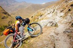 Il motociclista spinge la sua bicicletta su in alte montagne di Caucaso Immagine Stock