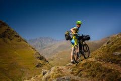 Il motociclista spinge la sua bicicletta su in alte montagne di Caucaso Fotografia Stock Libera da Diritti