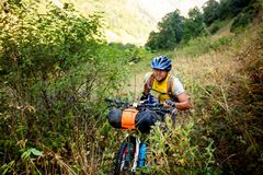 Il motociclista spinge la sua bicicletta su in alte montagne di Caucaso Fotografia Stock