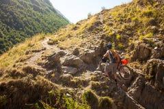 Il motociclista spinge la sua bicicletta su in alte montagne di Caucaso Fotografie Stock Libere da Diritti