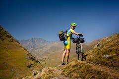 Il motociclista spinge la sua bicicletta su in alte montagne di Caucaso Immagini Stock