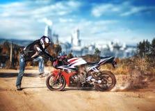 Il motociclista sta davanti al suo motociclo La bici sta filando la ruota posteriore slittamenti Mosche polvere e sabbia fotografia stock libera da diritti