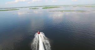 Il motociclo dell'acqua galleggia sull'ampio fiume Riflessione del cielo stock footage