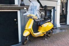 Il motorino giallo classico della vespa sta parcheggiato Immagini Stock