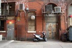 Il motorino ha parcheggiato in un alleato variopinto Fotografie Stock