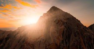 Il Mountain View con la siluetta della neve alla scena del tramonto con la caduta del sole ed il raggio si accendono, nuvole nel  Immagini Stock Libere da Diritti