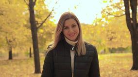 Il movimento della giovane donna adorabile sorridente allegra gode delle passeggiate in Autumn Park video d archivio