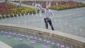 Il movimento divertente del mimo le sue mani come conduttore e controlla le fontane stock footage