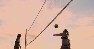IL MOVIMENTO LENTO, ANGOLO BASSO, FINE SU, SUN SI SVASA: Ragazza atletica che gioca i salti di beach volley nell'aria e nei colpi video d archivio