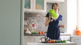 Il movimento lento del ballo divertente del cuoco della donna e canta con il ramo di lattuga mentre cucina nella cucina video d archivio