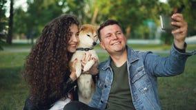 Il movimento lento del tipo bello che prende il selfie con la suoi moglie e cane nel parco, uomo allegro sta posando mentre donna archivi video