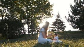 Il movimento lento della madre alimenta le verdure della figlia nel tramonto del chiarore stock footage
