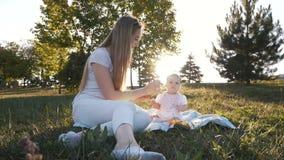 Il movimento lento della madre alimenta le verdure della figlia nel tramonto del chiarore video d archivio