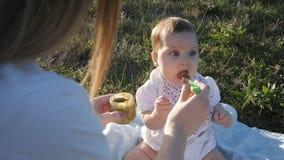 Il movimento lento della madre alimenta le verdure della figlia nel tramonto del chiarore archivi video