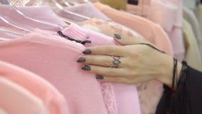 Il movimento lento delle mani del ` s della donna funziona attraverso uno scaffale dei vestiti, passante in rassegna in un boutiq archivi video
