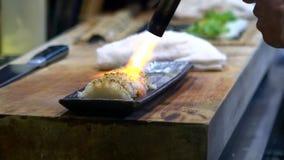 Il movimento lento di cheff brucia un pesce con la torcia per saldature per produce i sushi caramellare video d archivio