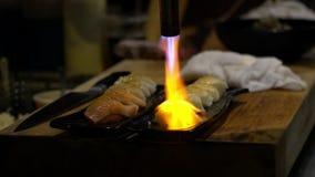 Il movimento lento di cheff brucia un pesce con la torcia per saldature per produce i sushi caramellare archivi video