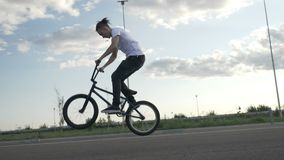 Il movimento lento di giovane aria metà di di pratica pedaling e di salto del motociclista si muove con la bici fuori nella via - stock footage