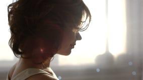 Il movimento lento di giovane donna sorridente sta incoraggiando un nuovo giorno, sorridente sui precedenti di luce solare di mat stock footage