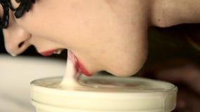 Il movimento lento di una donna sexy del yaung in un latte alimentare della maschera del pizzo gradisce un gatto stock footage