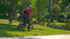Il movimento lento ha sparato di una giovane donna insegna al suo piccolo figlio a come guidare una bicicletta video d archivio