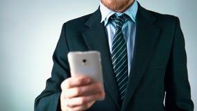 Il movimento lento, un uomo alla moda in un vestito utilizza un telefono cellulare guarda elegante video d archivio